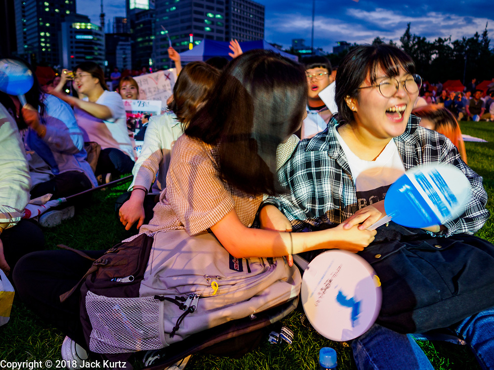 """15 JUNE 2018 - SEOUL, SOUTH KOREA:  Women cheer for patriotic entertainers during a rally to mark the anniversary of the signing of the June 15th North–South Joint Declaration between South Korea and North Korea. The Declaration was negotiated by late South Korean President Kim Dae-jung and North Korean leader Kim Jong-il and signed on 15 June 2000. It was a part of South Korea's """"Sunshine Policy,"""" which guides the South's relationship with North Korea. This year's observance of the anniversary was bolstered by the recent thawing in relations between North Korea and South Korea and the US.   PHOTO BY JACK KURTZ"""