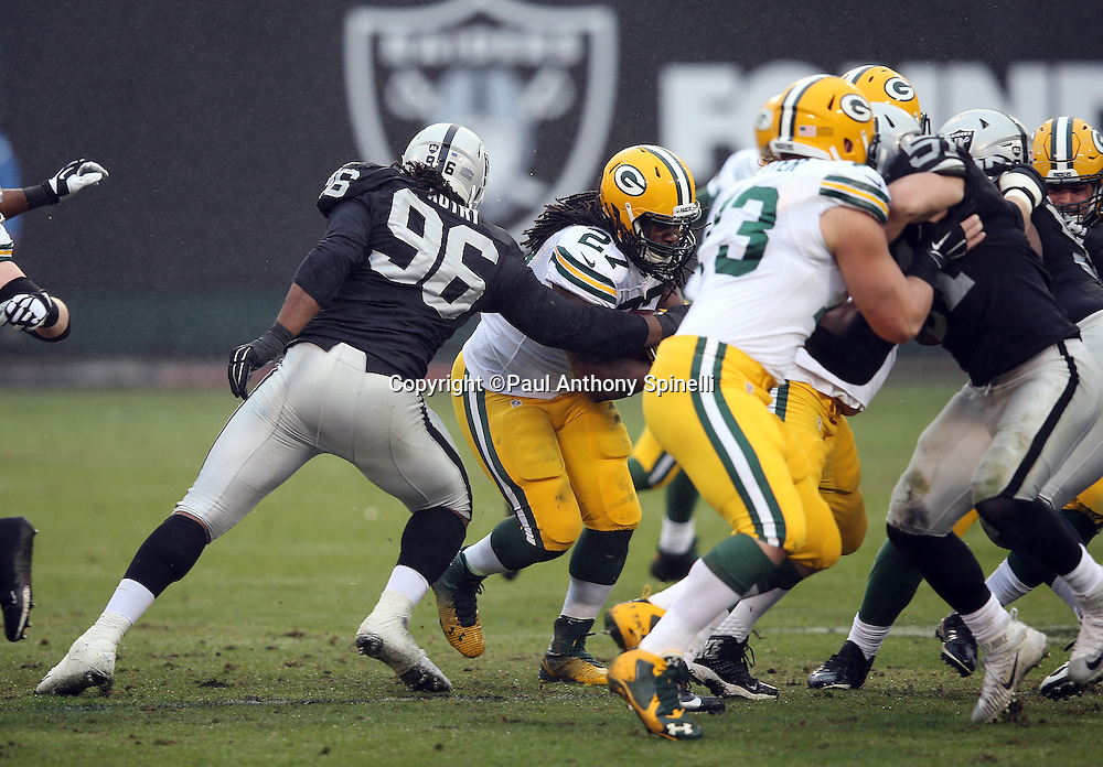 Oakland Raiders nose tackle Denico Autry (96) tackles Green Bay Packers running back Eddie Lacy (27) during the 2015 week 15 regular season NFL football game against the Green Bay Packers on Sunday, Dec. 20, 2015 in Oakland, Calif. The Packers won the game 30-20. (©Paul Anthony Spinelli)