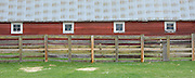 Washington, Chewelah. A red barn with four square windows and aluminum roofing with fence and grass. . PLEASE CONTACT US FOR DIGITAL DOWNLOAD AND PRICING.