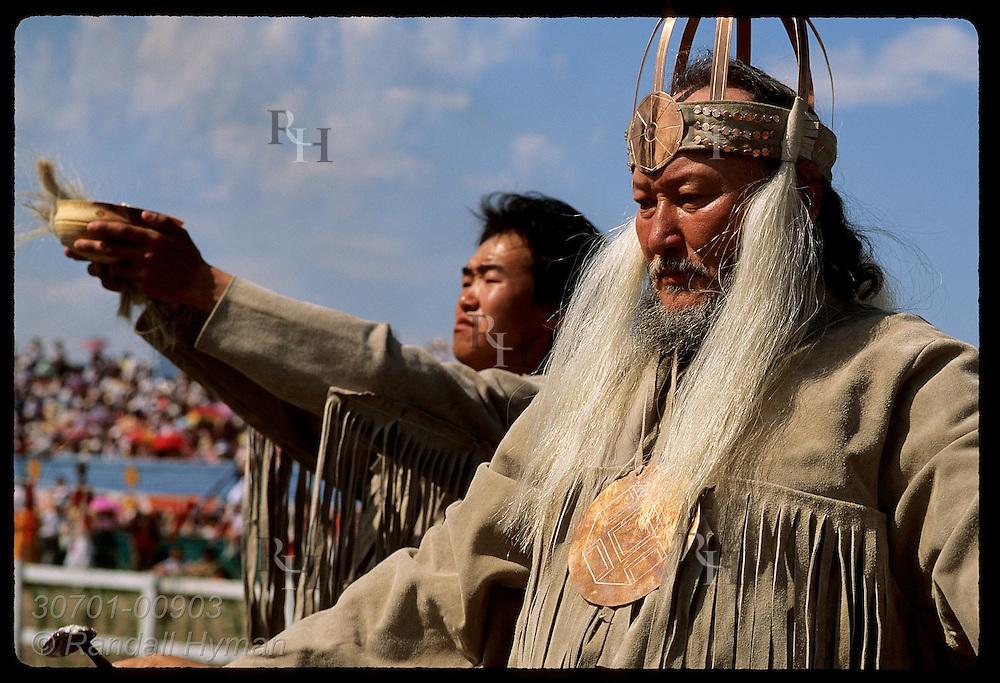 Shaman prays as asst holds bowl skyward at performance of ancient Olonkho epic;Ysyakh fest,Yakutsk Russia