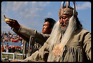 Shaman prays as asst holds bowl skyward at performance of ancient Olonkho epic;Ysyakh fest,Yakutsk Russia