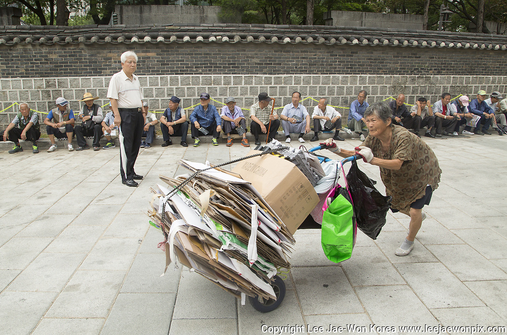 A South Korean woman pushes a cart containing waste papers which she collected to sell, on the way to a rag-and-bone merchant as elderly people in background queue up for free lunch from a Buddhist temple in Seoul, South Korea on July 17, 2017. Photo by Lee Jae-Won (SOUTH KOREA) www.leejaewonpix.com