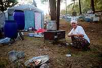 Female migrant bee keeper next to her temporary home preparing food for meal  in pine forest near Akyaka in Turkey.
