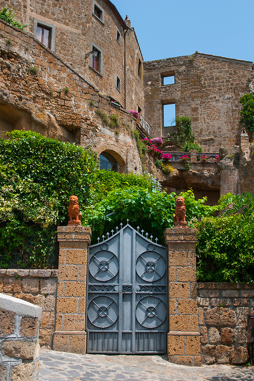An entrance along the climb to reach the village of Civita di Bagnoregio.<br /> Civita di Bagnoregio is a town in the Province of Viterbo in central Italy, a suburb of the comune of Bagnoregio, 1 kilometre (0.6 mi) east from it. It is about 120 kilometres (75 mi) north of Rome. Civita was founded by Etruscans more than 2,500 years ago. Bagnoregio continues as a small but prosperous town, while Civita became known in Italian as La citt&agrave; che muore (&quot;The Dying Town&quot;). Civita has only recently been experiencing a tourist revival. The population today varies from about 7 people in winter to more than 100 in summer.The town was placed on the World Monuments Fund's 2006 Watch List of the 100 Most Endangered Sites, because of threats it faces from erosion and unregulated tourism.