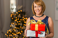 Portrait of smiling woman holding Christmas presents at home