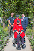 Matthew Keightley and Tom Stimpson   MBE. RAF Veteran with Chelsea Pensioners Jim Lycett and Frank Mouque (wheelchair) on the Hope on the Horizon garden.  The<br /> &lsquo;Hope on the Horizon&rsquo; garden in aid of Help for Heroes: produced by building and landscaping firm Farr and Roberts&rsquo;, making their debut; designed by Matthew Keightley (29), as a result of his brother Michael&rsquo;s involvement with the armed forces, having served on four tours to Afghanistan and due for his fifth this year; and sponsored by the David Brownlow charitable foundation. The garden layout is based on the shape of the Military Cross, the medal awarded for extreme bravery. Granite blocks will represent the soldiers&rsquo; physical wellbeing and the planting represents their psychological wellbeing at various stages of their rehabilitation. Both evolve through the garden from a rough, unfinished, over-grown beginning through to a perfectly sawn, structured end. An avenue of hornbeams draws the attention through the entire garden to a sculpture resembling a hopeful horizon; a reminder to the soldiers that they all have a bright future ahead. As well as areas to recline and reflect, the garden offers focal points all the way through. Cool, calming colours are used throughout, helping to emphasise the fact that it will be a serene, contemplative space. After the Show, the garden will be moved and set within the grounds at Help for Heroes Recovery Centre at Chavasse VC House in Colchester, Essex. The garden will offer a serene, peaceful haven to contemplate and inspire a bright future and to support the challenging journey to recovery. The Chelsea Flower Show 2014. The Royal Hospital, Chelsea, London, UK