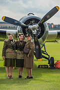 Re-enactors in perod costume pose with planes - Duxford Battle of Britain Air Show taking place during IWM (Imperial War Museum) Duxford's centenary year. Duxford's principle role as a Second World War fighter station is celebrated at the Battle of Britain Air Show by more than 40 historic aircraft taking to the skies.