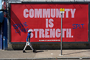 As the UK's Conornavirus pandemic lockdown continues, but with travel restrictions and social distancing rules starting to ease after three months of closures and isolation, a boy walks past a billboard that has appeared across the capital, telling Londoners that Community is Strength and that staying together is best, while someone has added a more confusing message asking for others to save lives by spitting, a breach of pandemic health guidelines, on 9th June 2020, in south London, England.