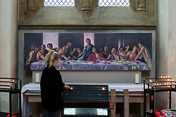 © Licensed to London News Pictures. 04/07/2020. ST ALBANS, UK.  A visitor lights a candle in front of a version of the Last Supper, with Jesus as a black man, at St Albans Cathedral in support of Black Lives Matter.  The 8ft 8in-high (2.6m) high-resolution print of Lorna May Wadsworth's version of Leonardo da Vinci's 15th century masterpiece is on display above the Altar of the Persecuted in the North Transept of the cathedral and shows Tafari Hinds, a Jamaican model, as Jesus The artwork is part of a prayer installation to mark the cathedral's reopening after coronavirus pandemic lockdown restrictions were eased by the UK government.  Photo credit: Stephen Chung/LNP