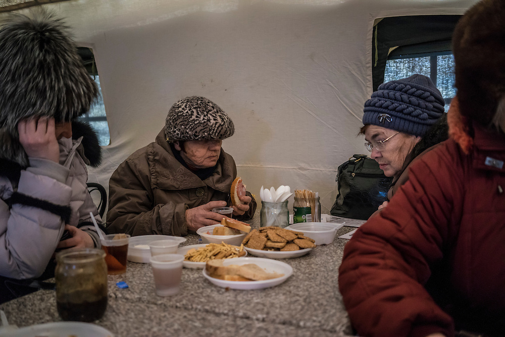 People displaced by fighting between pro-Russia rebels and Ukrainian forces in Eastern Ukraine inside a tent that serves hot meals at a processing center for internally displaced people located at the train station on Monday, February 9, 2015 in Slovyansk, Ukraine.