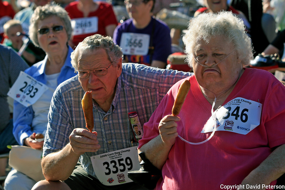 "Joan and Earnest Mason, from Oskaloosa, Iowa, look less than pleased with having to wait to eat their corn dogs at the Iowa Corn Dog Chomp held August 7th at the Iowa State Fair.  Over 8,500 corn dogs were passed out so that fairgoers could be part of a ""world record""  for consuming the most corn dogs at once.  For Earnest, it was the first corn dog that he had ever eaten."