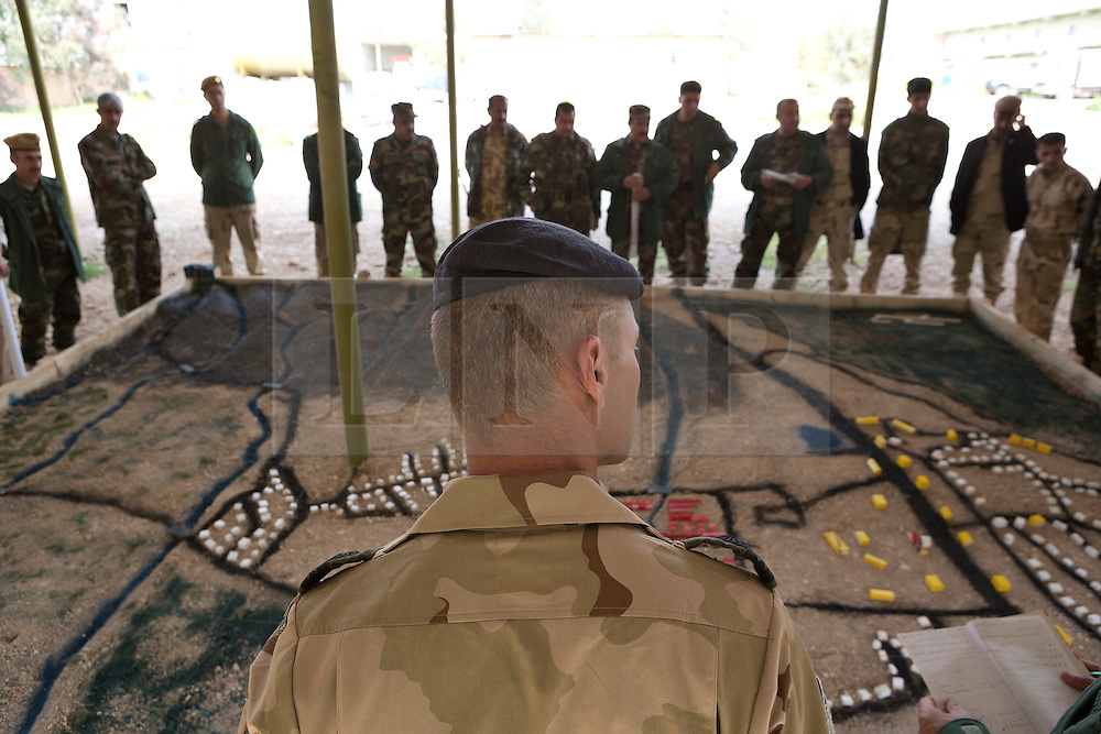 © Licensed to London News Pictures. 30/03/2015. Erbil, Iraq. A Dutch coalition forces instructor instructs peshmerga officers on operational planning using a sand box model at a military training area near Erbil, Iraq.<br /> <br /> The training is part of a four week long package, the first to be held with a complete peshmerga battalion, run by coalition forces mobile training teams (MTT) in Kurdistan with the aim to make the peshmerga more efficient in combatting the Islamic State. Photo credit: Matt Cetti-Roberts/LNP