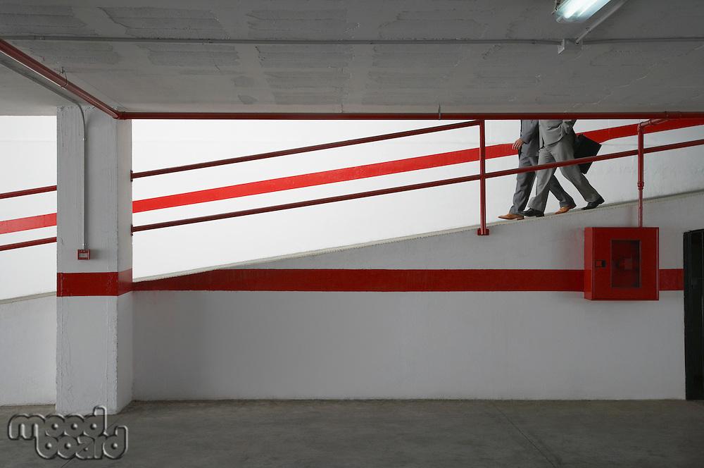 Two businessmen walking down ramp in parking garage