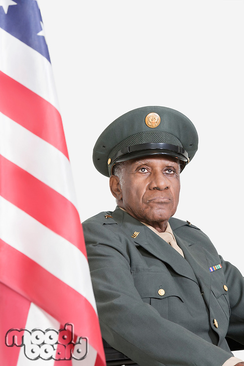 Senior male US military officer with American flag against gray background