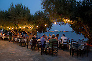 A seafront taverna at dusk in Platis Ghialos, Sifnos, The Cyclades, The Greek Islands, Greece