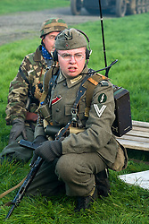 "A Re-enactor portraying a Obergefreiter of the Grossdeutschland Panzer Grenadier Division  during a battle battle re-enactment on Pickering Showground. He is wearing an Iron Cross 2nd Class ribbon and a ""Blitzbündel"" or thunderbolt Badge on his sleeve above his rank marking him as a signals radio operator. He carrying a Field radio and is wearing a side cap and earphones"