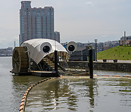 Baltimore, MD, USA --April 13, 2019-- The inner harbor water wheel scoops up debris in the harbor for eventual disposal.