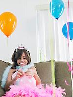 Young girl (7-9) on sofa preparing birthday balloons