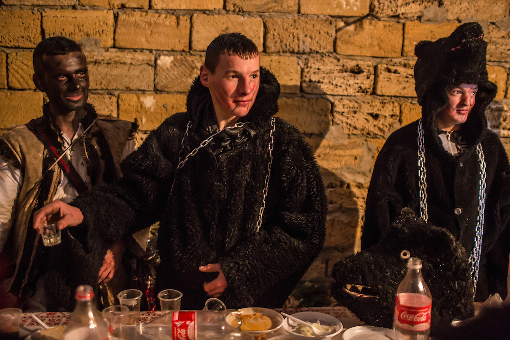 Revelers in costume take a break from their celebrations of the Malanka Festival to eat lunch on Thursday, January 14, 2016 in Krasnoilsk, Ukraine. The annual celebrations, which consist of costumed villagers going in a group from house to house singing, playing music, and performing skits, began the previous sundown, went all night, and will last until evening.