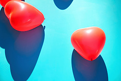 Red Heart Shaped Party Balloons on Blue Background