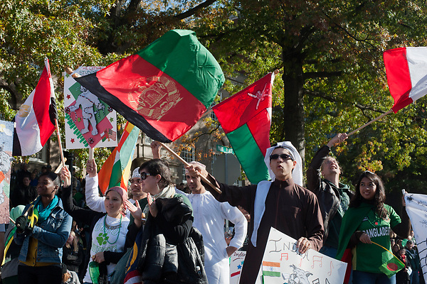 Students and members of the Ohio University international community wave flags during the homecoming parade. Photo by: Ross Brinkerhoff.