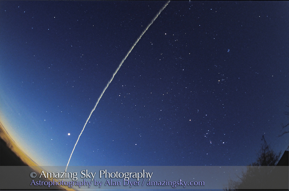 Re-Entry of Shuttle STS79 over southern Alberta, September 26, 1996 at dawn.<br /> <br /> Shuttle is gone here, moved off over Montana, leaving greenish train behind &mdash; the ionized &quot;smoke&quot; trail left by Shuttle. Train persisted for several minutes. Here it is beginning to spread out.<br /> <br /> This image taken immediately after #2<br /> <br /> Orion and winter-fall sky constellations visible. Venus is bright object left of smoke train. <br /> <br /> 16mm full-frame fish-eye lens. Ektachrome 400 slide film. Untracked exposure for about 40 seconds.
