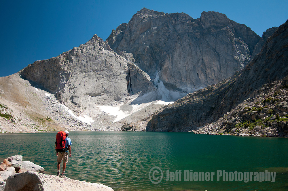 A young man admires the view of Temple Peak in the Wind River Mountains, Wyoming.
