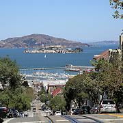 A tourist snaps a photo of Alcatraz Island and the marina in San Francisco, California on Sunday, August 24,  2014. (AP Photo/Alex Menendez)