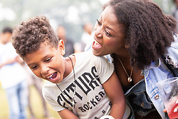 © Licensed to London News Pictures . 12/08/2018. Manchester , UK . Son HARMEN KASMA (seven) and his mother JANICE KASMA (33) , from Sale . The second day of the annual Caribbean Carnival in Alexandra Park in Moss Side , celebrating music , food and Afro-Caribbean culture . A nearby shooting overnight lead to at least ten people injured . Ten people are in hospital . Photo credit : Joel Goodman/LNP