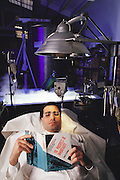 USA_SCI_CRY_08_xs .Cryonics: Dr Avi Ben-Abraham, of Trans Time Inc., a cryonics company of Oakland, California. Cryonics is a speculative life support technology that seeks to preserve human life in a state that will be viable and treatable by future medicine. Cryonics involves freezing whole human bodies, organs or pet cats & dogs, in liquid nitrogen (tank in background) to await a future thaw. Cryonicists claim that medical science in the future may offer a cure for cancer or the restoration of youth, and that their methods of preservation might offer some people an opportunity to benefit from these advances. Conventional cryobiology methods for freezing organs (for organ transplants, for example) are plagued by problems of intracellular ice crystal formation, which destroys their component cells. Dr. Ben Abraham is reading ?the Prospect of Immortality? and is wearing a bracelet that identifies him as a cryonic patient should he be found dead. MODEL RELEASED 1987.