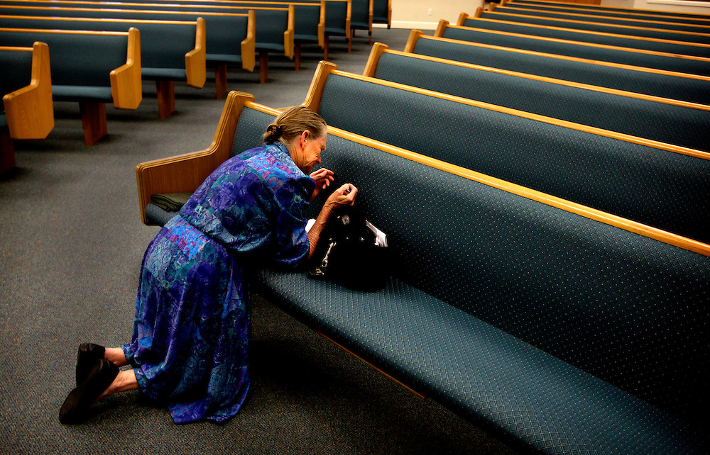 """Katherine Smith, 71, says a prayer during her weekly prayer group at Assembly of God in Naples. Smith may be joined by up to a dozen other women, who divide up all the prayer requests from other members of the church, but since no one else could make it, Smith had to say all 36 of them herself. Church means everything for Smith, and she attends three days a week. """"I can be down and out, but then I go to church and after I feel better,"""" Smith said. Greg Kahn/Staff"""
