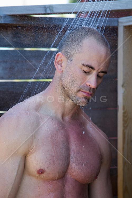 man relaxing in an outdoor shower