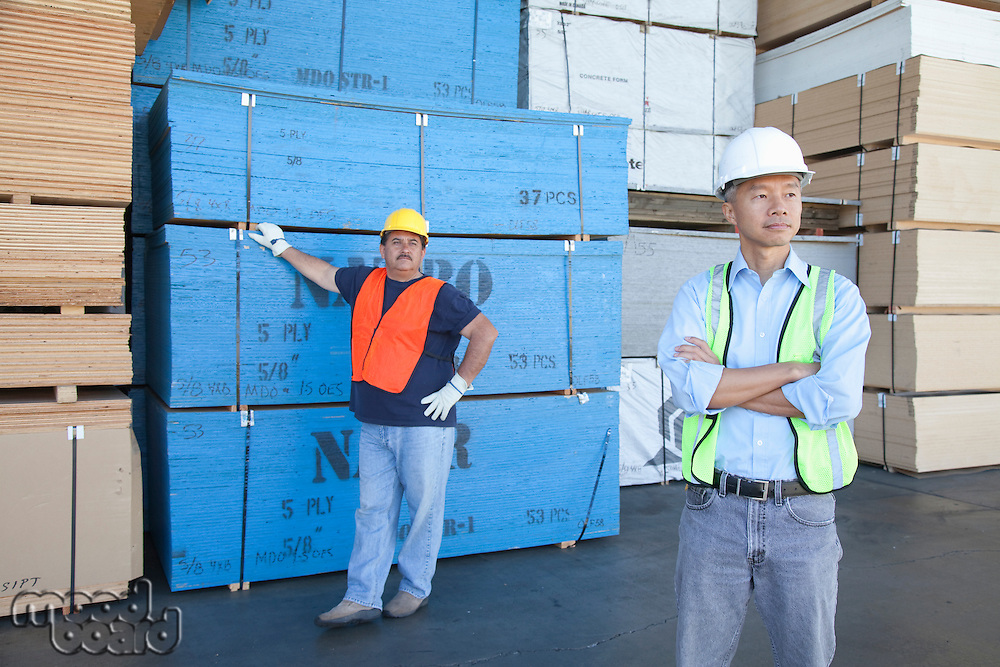 Male warehouse workers standing in front of stack of plywood