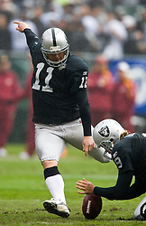 December 13, 2009; Oakland, CA, USA;  Oakland Raiders kicker Sebastian Janikowski (11) kicks a field goal in the rain against the Washington Redskins during the first quarter at Oakland-Alameda County Coliseum.  Washington defeated Oakland 34-13.
