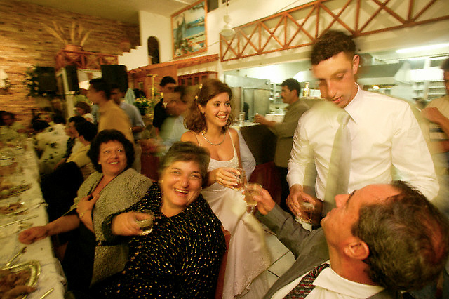 October 2003, Agia Anna, Naxos, Greece --- Newlyweds walk around and toast with friends and family during their wedding reception in Agia Anna, Greece. --- Image by © Owen Franken/CORBIS