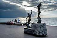 Evening light on the Malecon of Puerto Vallarta, sunbeams break through clouds over men sitting w/ bicycles and Triton and Mermaid sculpture by artist Carlos Espino, Bay of Banderas behind.