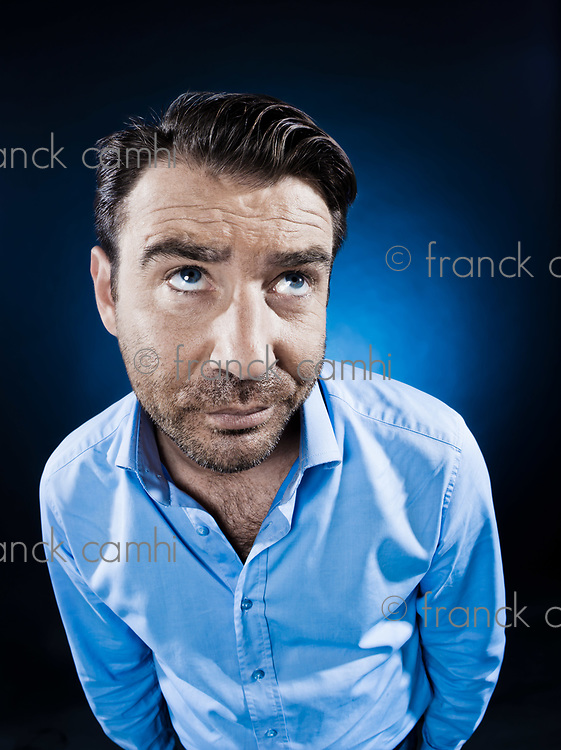 caucasian man unshaven portrait looking up pensive isolated studio on black background