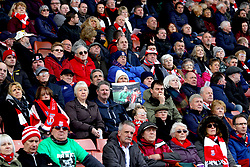 A fan in the stands holds up a photo as the funeral service for Gordon Banks is shown on the big screens at the bet365 Stadium, Stoke.
