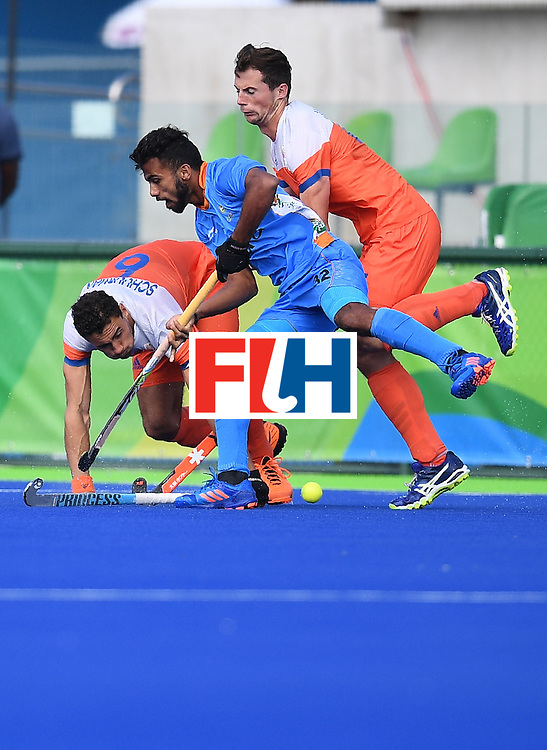 Netherland's Glenn Schuurman (L) and Sander Baart (R) fight for the ball  with India's Chandanda Thimmaiah during the men's field hockey Netherland's vs India match of the Rio 2016 Olympics Games at the Olympic Hockey Centre in Rio de Janeiro on August, 11 2016. / AFP / MANAN VATSYAYANA        (Photo credit should read MANAN VATSYAYANA/AFP/Getty Images)