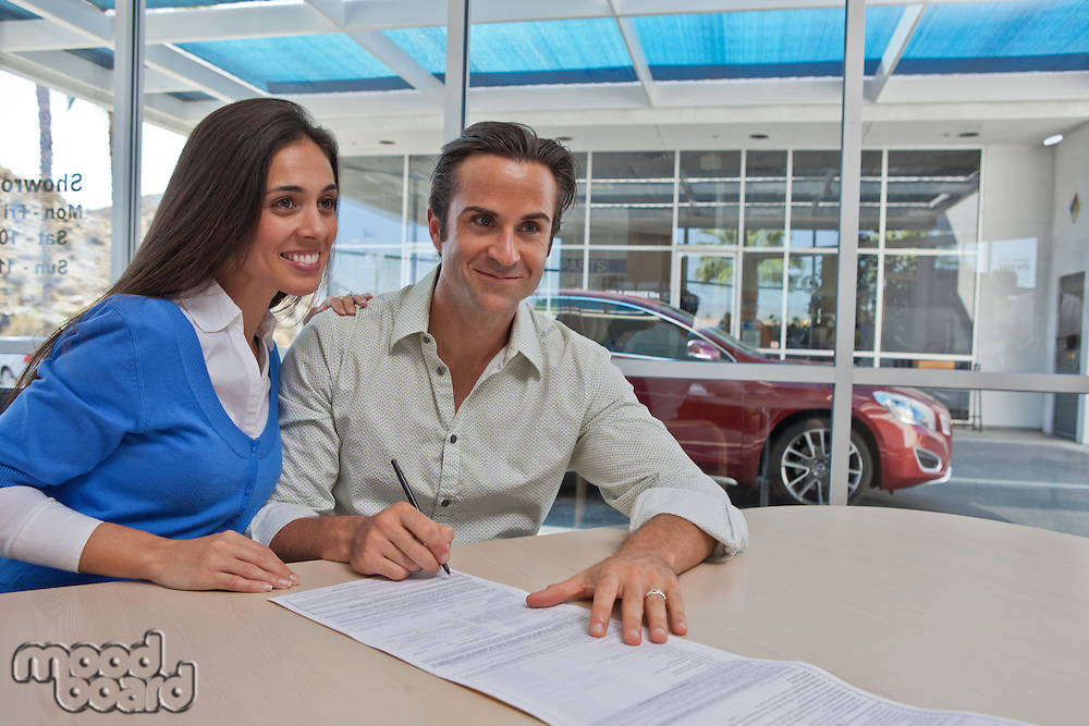 Couple signing documents for new car