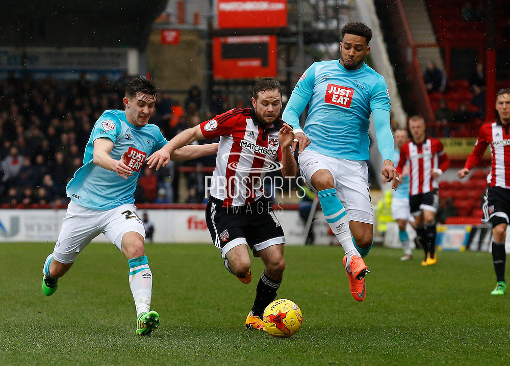 Brentford midfielder Alan Judge attempts to get past Derby County Defender Cyrus Christie and Derby County Midfielder Jamie Hanson during the Sky Bet Championship match between Brentford and Derby County at Griffin Park, London, England on 20 February 2016. Photo by Andy Walter.