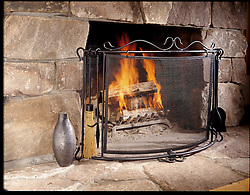fireplace. Stone fireplace with grate and tools
