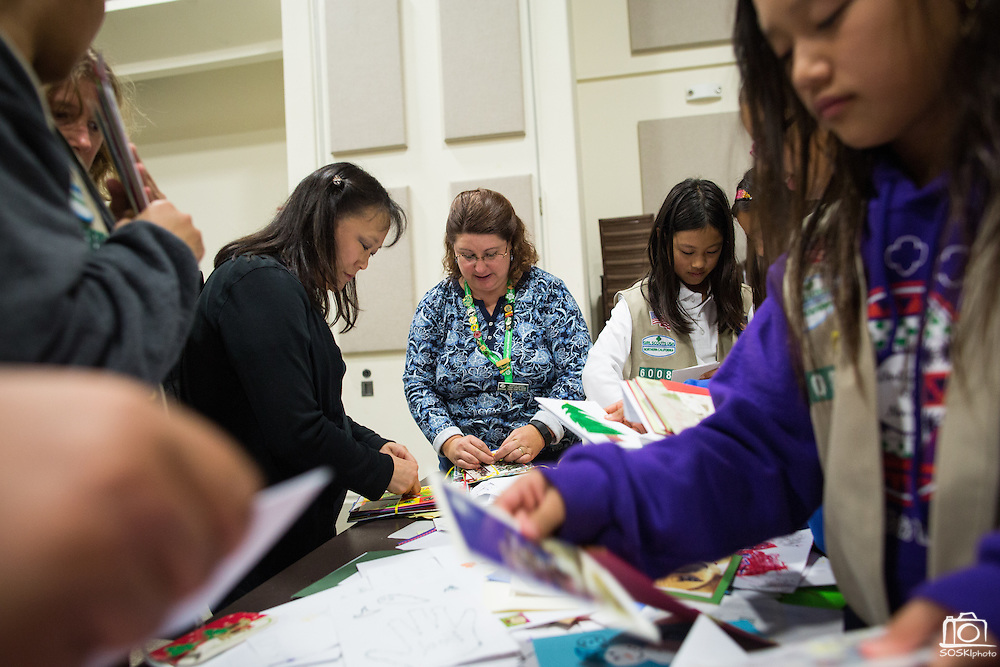 Michelle Eacret, center, helps girl scouts and their parents sort and bundle Holiday Cards created special for the U.S. Military during the Girl Scout USA of Northern California Operation Holiday Cards packing event at Mount Olive Ministries in Milpitas, California, on November 18, 2015. Eacret created Operation Holiday Cards 13 years ago, and now helps generate more than 6,000 cards for the U.S. Military. (Stan Olszewski/SOSKIphoto)