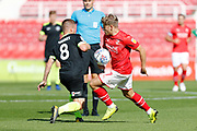 Swindon Town winger Lloyd Isgrove is challenged by Macclesfield Town midfielder Jay Harris during the EFL Sky Bet League 2 match between Swindon Town and Macclesfield Town at the County Ground, Swindon, England on 14 September 2019.
