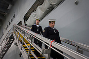 Sailors walk down the gangplank beneath the giant hull of their ship during a tour by the general public on-board the Royal Navy's aircraft carrier HMS Illustrious during a public open-day in Greenwich. Illustrious docked on the river Thames, allowing the tax-paying public to tour its decks before its forthcoming decommisioning. Navy personnel helped with the PR event over the May weekend, historically the home of Britain's naval fleet.