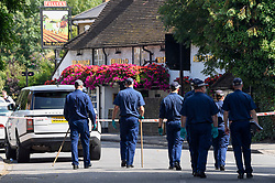 © Licensed to London News Pictures. 25/08/2019. SOUTHALL, UK.  Police officers conduct a search adjacent to St Mary's Avenue near Southall in west London.  It is reported that a man in his 60s was stabbed outside The Plough pub (pictured) on Tentelow Avenue in the early evening of 24 August and stumbled to nearby St Mary's Avenue to seek aid from a residence.  Police were called at 6.41pm, paramedics and air ambulance crews attended but the man passed away.  A man in his 30s has been arrested on suspicion of murder.  The investigation continues. Photo credit: Stephen Chung/LNP