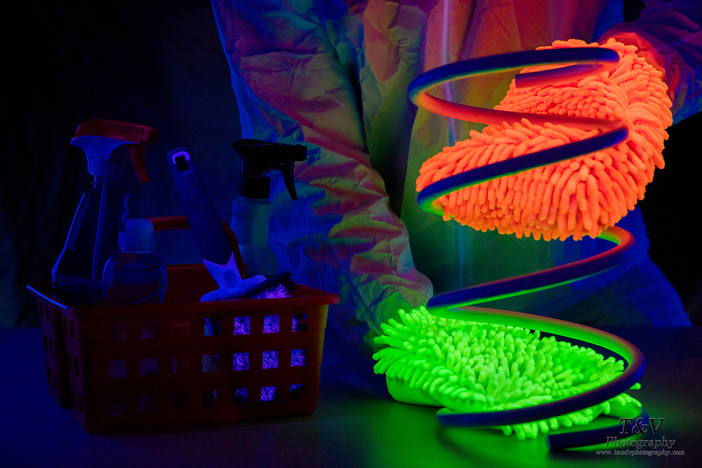 A large spring is cleaned with glowing microfiber wash mits. Blacklight photography.