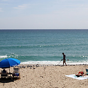 Beach goers enjoy the sun in South Florida. Using a magnetometer looking for treasure.