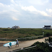 A beach goer with his surfboards heads back from Cisco Beach, Nantucket, late in the day. Nantucket Island, Massachusetts, USA. Photo Tim Clayton