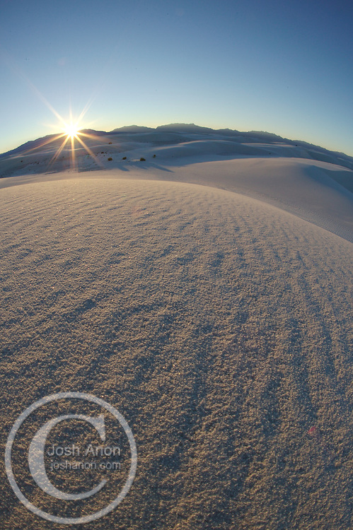 The sun rises over the shapely dunes at White Sands National Monument, New Mexico.